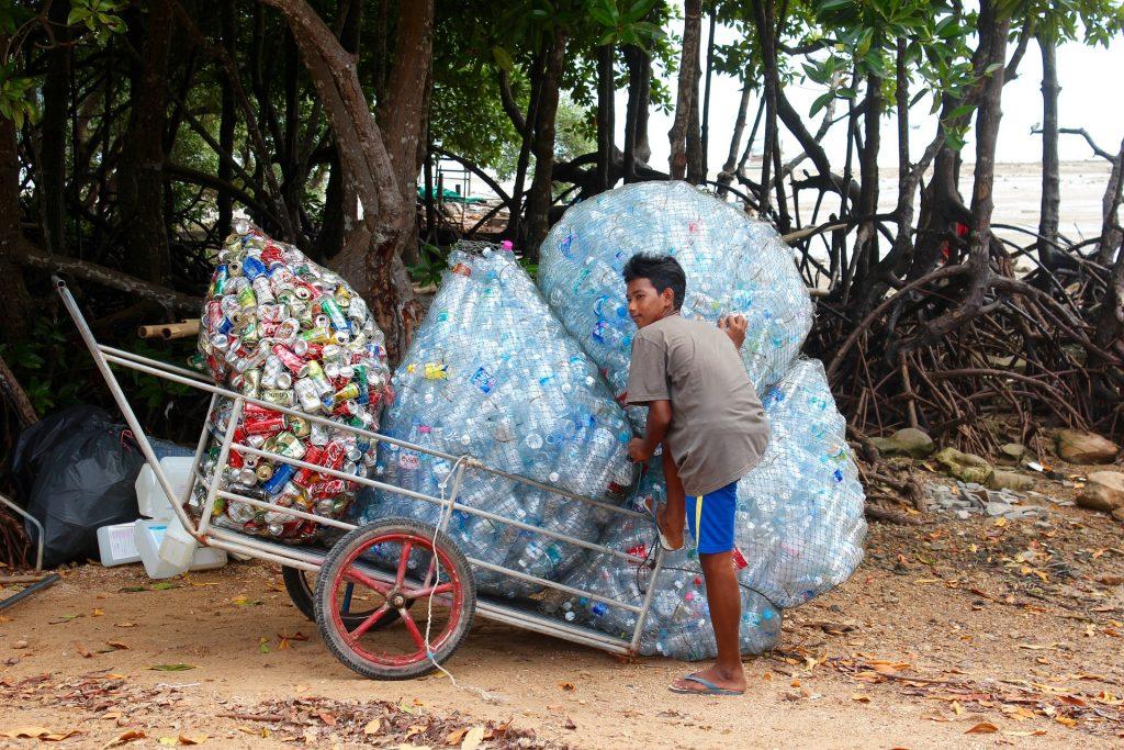 Junge sammelt Plastik am Strand seiner Heimatinsel